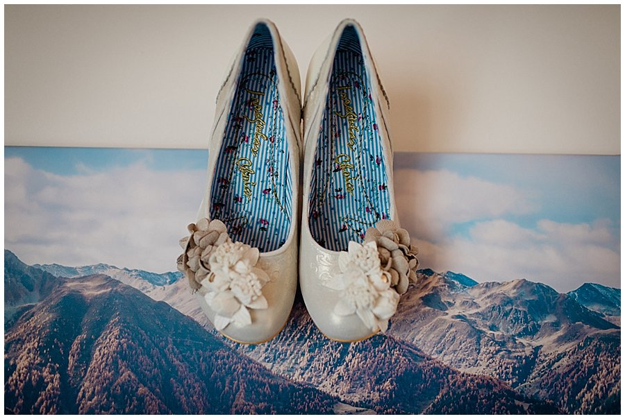 Irregular Choice Wedding Shoes hanging on a canvas picture of mountains in a hotel room