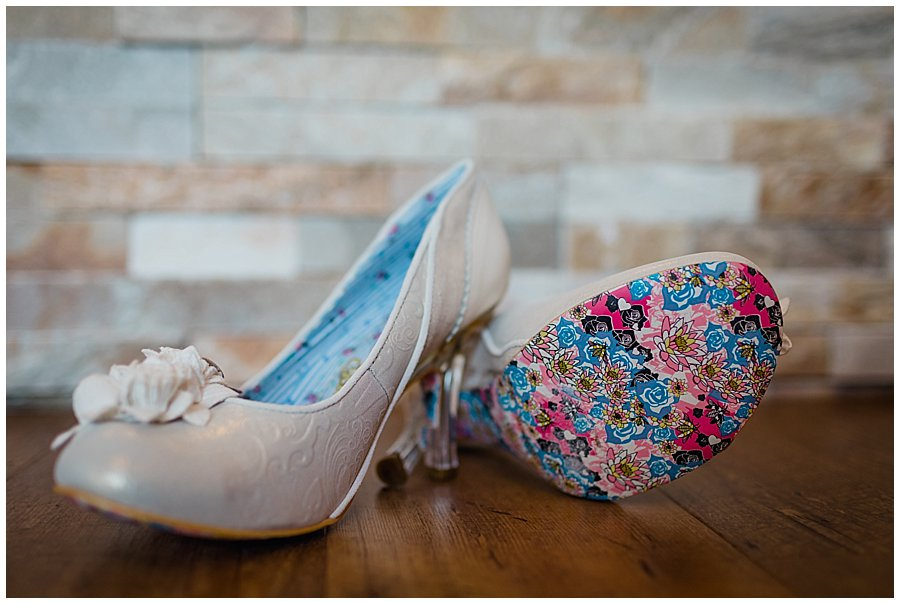 Irregular Choice Wedding Shoes lying on the bathroom floor. Shoes showing colourful soles.