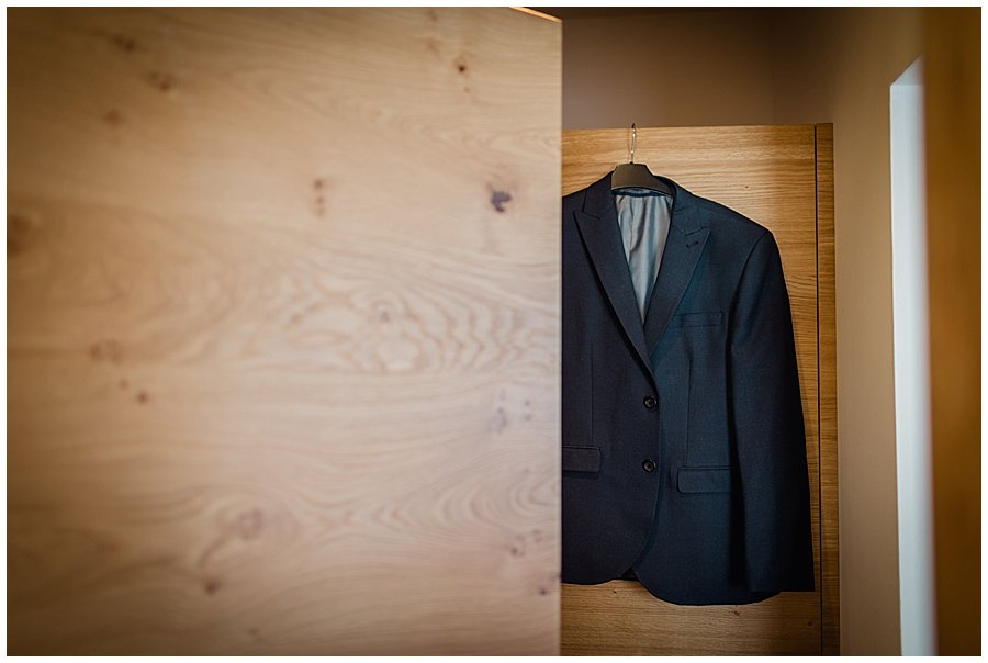 The groom Wayne's suit hanging on the wardrobe door in his hotel room