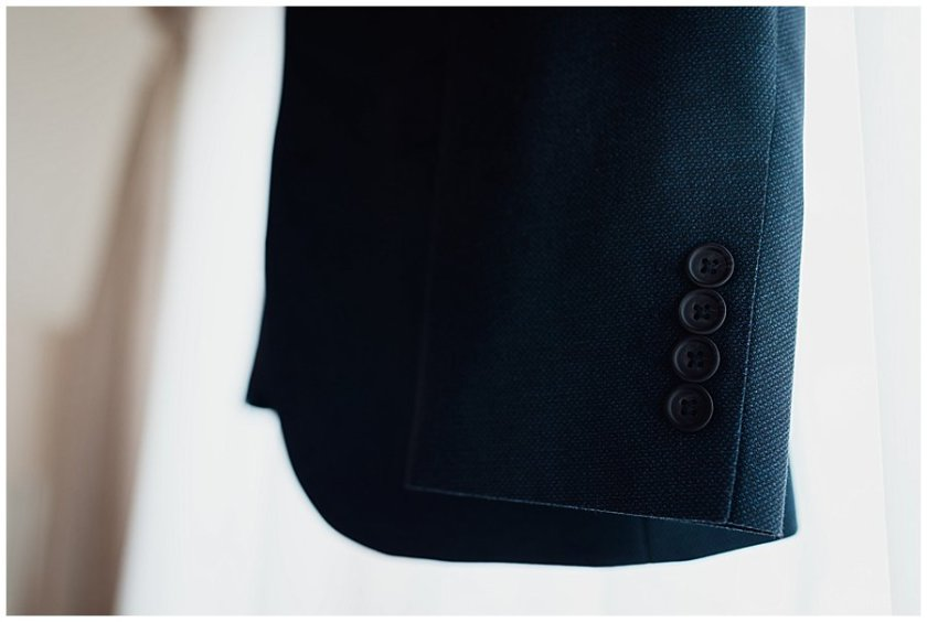 Close up of the buttons on the sleeve of Wayne, the groom's suit