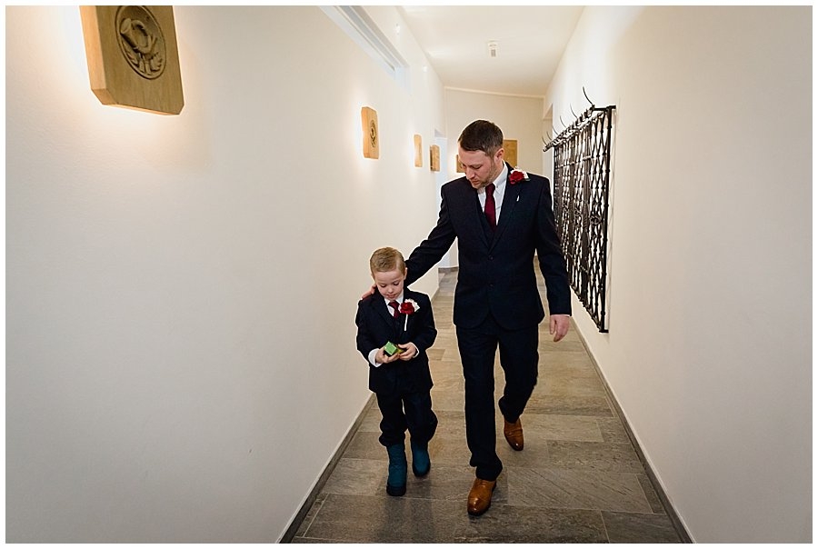 Wayne and his son Ethan walking down a corridor as they prepare to depart for the wedding