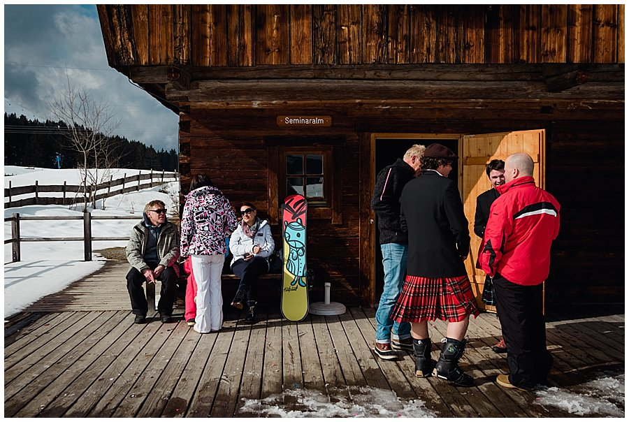 A snowboard rests against the wall of the cabin as the wedding guests stand outside chatting