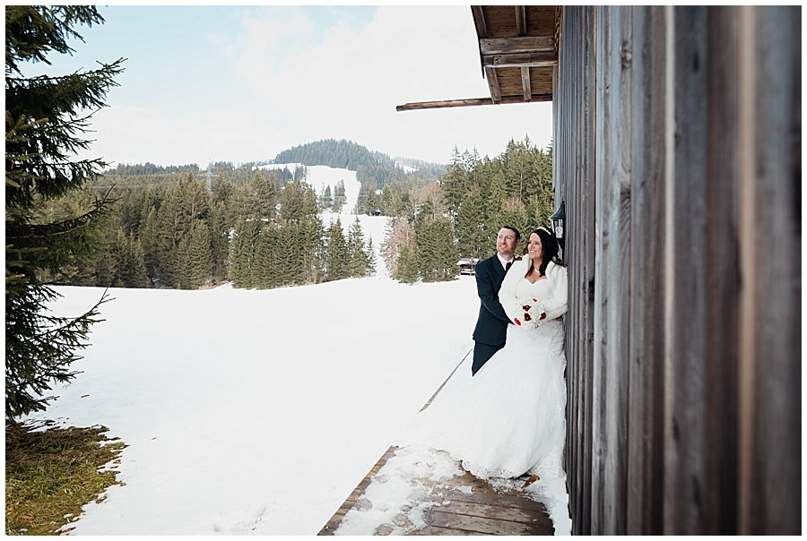 Wayne standing behind Michelle leaning against the wooden hut wall looking across to the mountains
