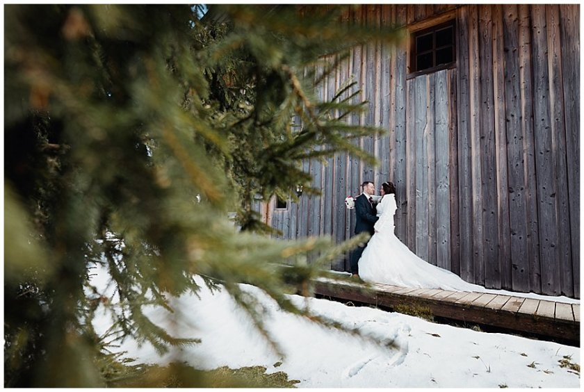 A picture of Wayne & Michelle embracing against the side of the hut, taken through the branches of a pine tree