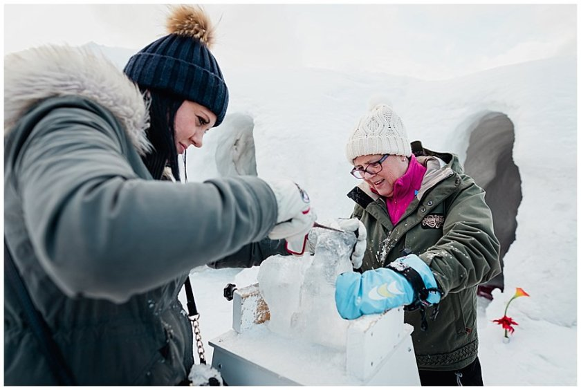 Two ladies carve an animal out of ice