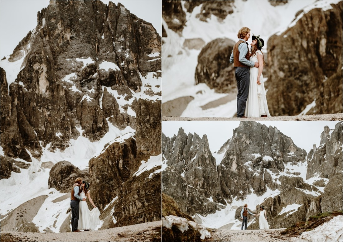 The bride and groom dance on a ridge in the Dolomites with the snow-capped mountains behind them. Photography by Wild Connections Photography