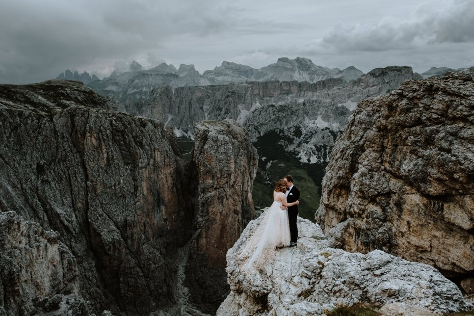 Bride and groom standing on a cliff in the Dolomites after their hiking elopement. Photo by Wild Connections Photography