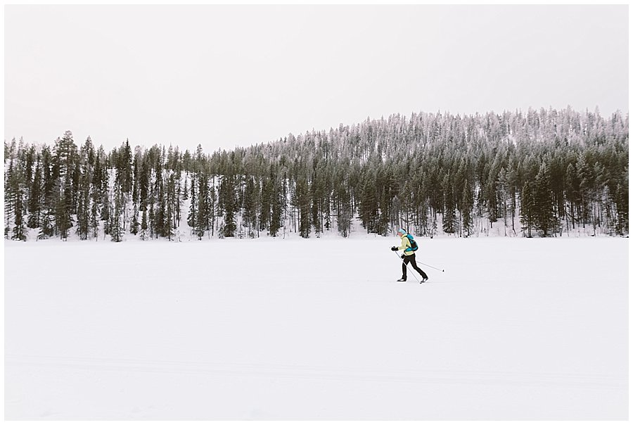 a single cross country skier glides across a frozen lake in Levi Finland by Wild Connections Photography
