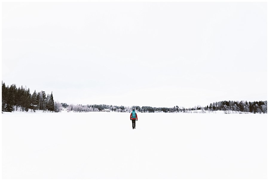 Menno walks across a frozen lake in Levi Finland by Wild Connections Photography