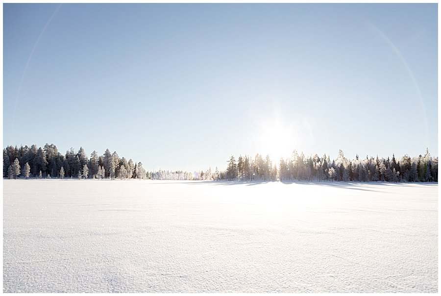 The sun shines from behind the trees over a frozen lake in Levi Finland by Wild Connections Photography