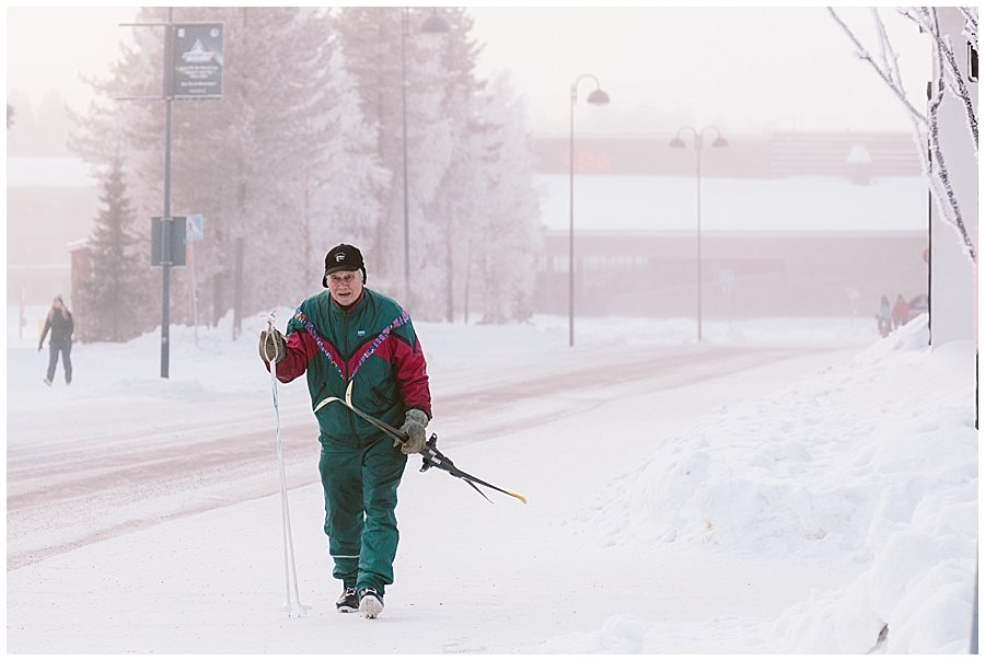 An old man walks through the town with cross country skis in Levi Finland by Wild Connections Photography