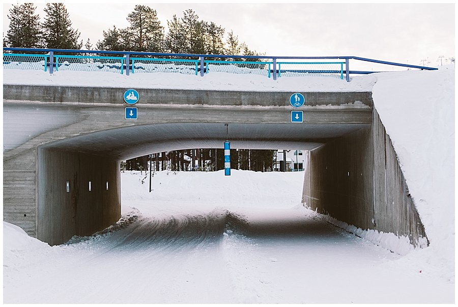 A bridge in with a walking and a snowmobile track in Levi Finland by Wild Connections Photography
