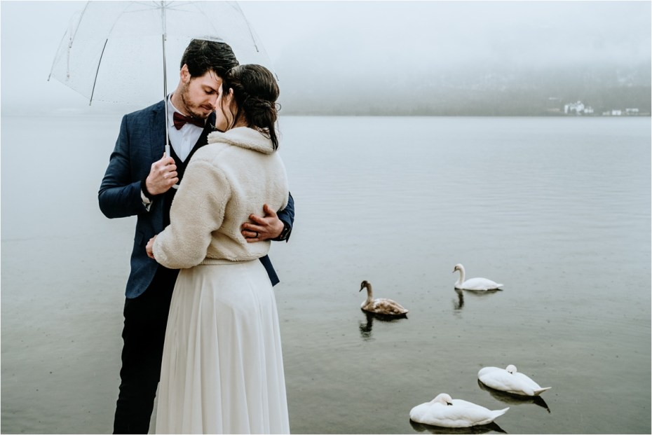 Swans swim on the lake behind the bride and groom after their elopement in Hallstatt Austria. Photos by Wild Connections Photography