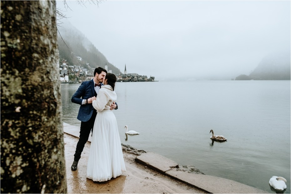 Anna & John kiss by the Hallstatt Lake on their wedding day. Photos by Wild Connections Photography