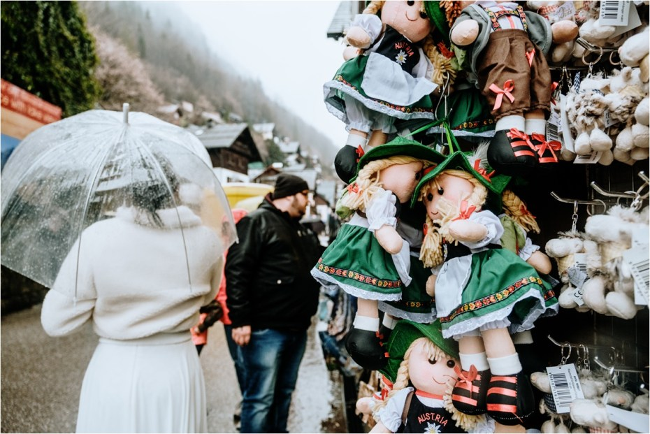 Bride and groom walk past a souvenir stand in Hallstatt Austria. Photos by Wild Connections Photography