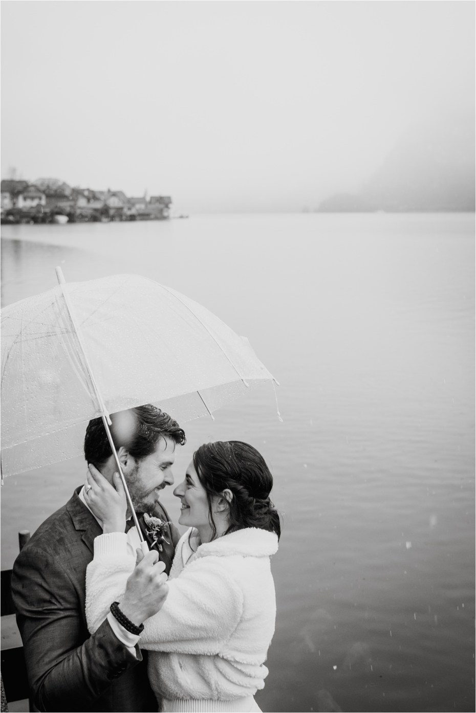 Bride and groom shelter under an umbrella in the rain. Photos by Wild Connections Photography