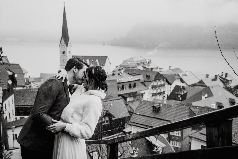 A bride and groom kiss on the stairs of Hallstatt in Austria on their wedding day. Photos by Wild Connections Photography
