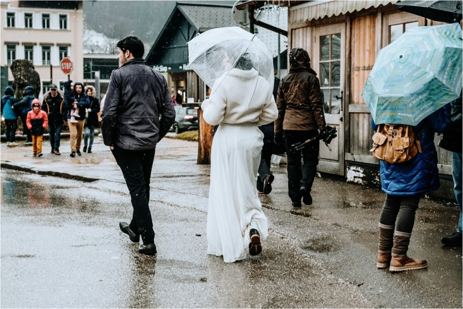 Bride and groom walk through Hallstatt in the rain. Photos by Wild Connections Photography