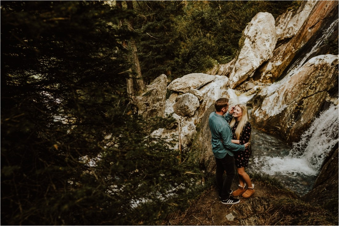 Kai stroked Sarah's hair during their waterfall engagement in Austria by Wild Connections Photography