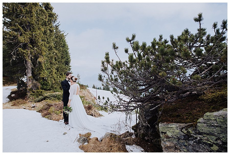 Honeymoon shoot in Austria Groom kisses bride on the forehead as they stand in the snow on top of a mountain by Wild Connections Photography
