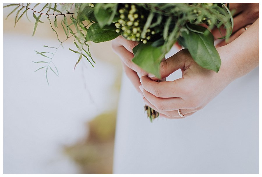 Close up of Susana's hands holding the bouquet and her wedding ring