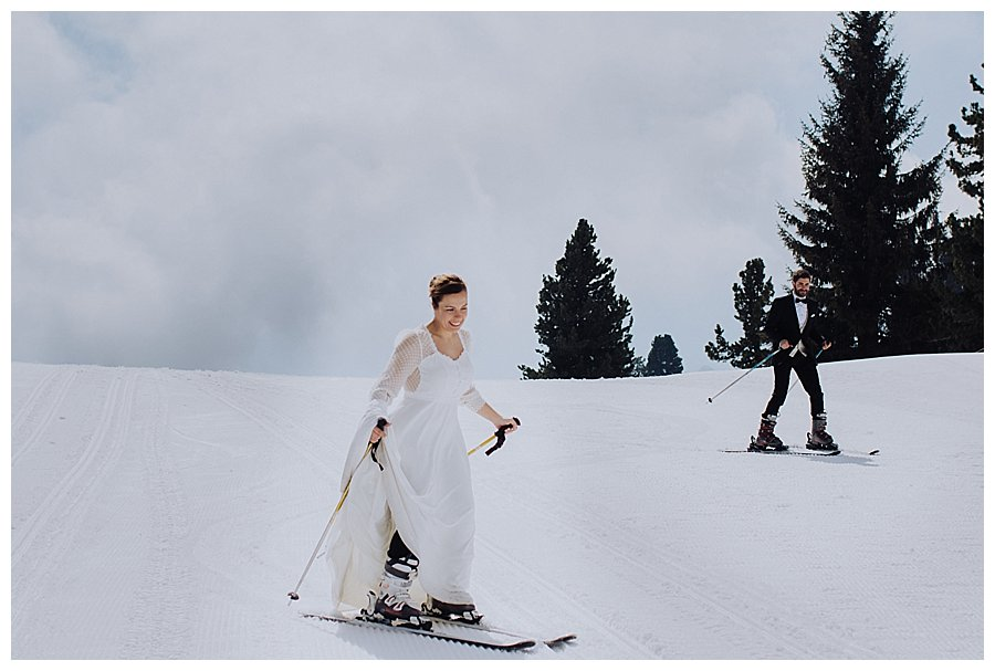 Skiing bride and groom in Kaltenbach in Zillertal during a honeymoon trash the dress shoot in Austria by Wild Connections Photography