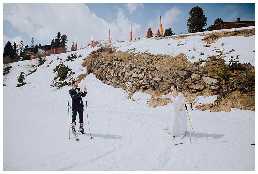 Bride throwing a snowball at the groom as they stand on skis