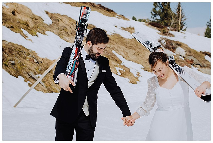 Bride and groom with skis over their shoulders walking hand in hand