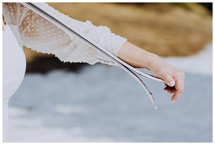 Close up of the bride holding skis