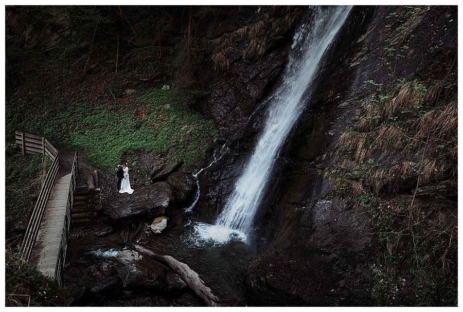 Wide angled picture of a bride and groom standing by a waterfall in Austria