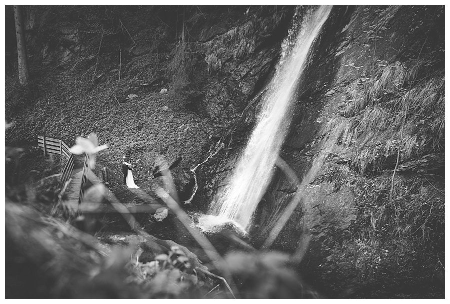 A black and white image of a bride and groom standing at the base of a waterfall