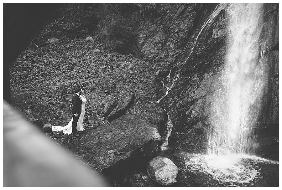 Bride and groom standing side by side looking up at the waterfall crashing down next to them
