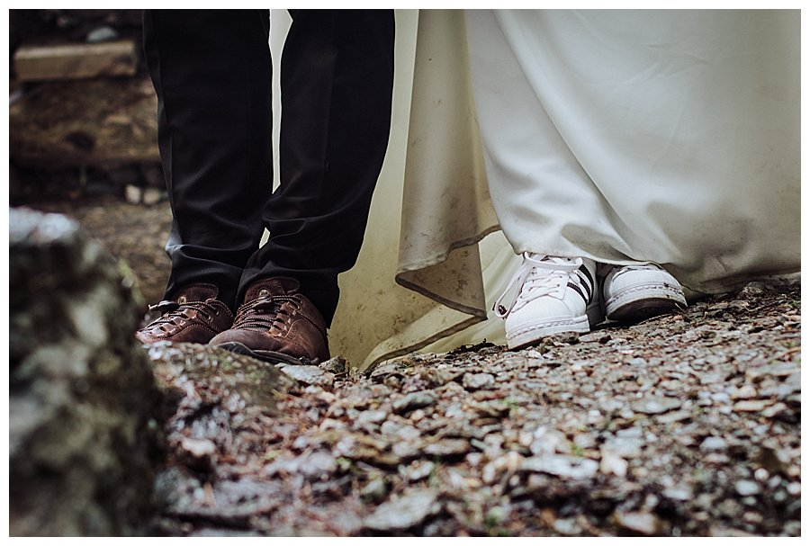 A picture of the bride and groom's shoes with the bride in Adidas trainers