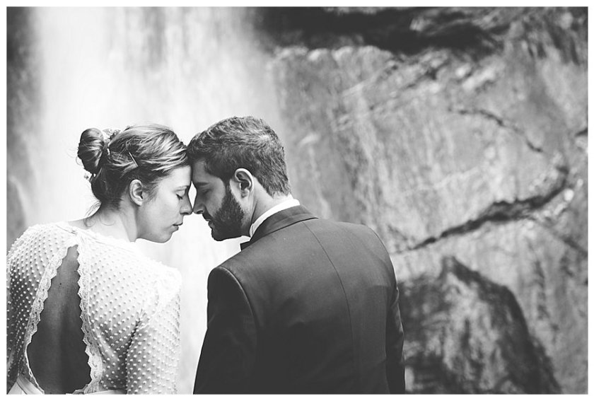 Bride and groom leaning to each other with their foreheads together with a waterfall in the background