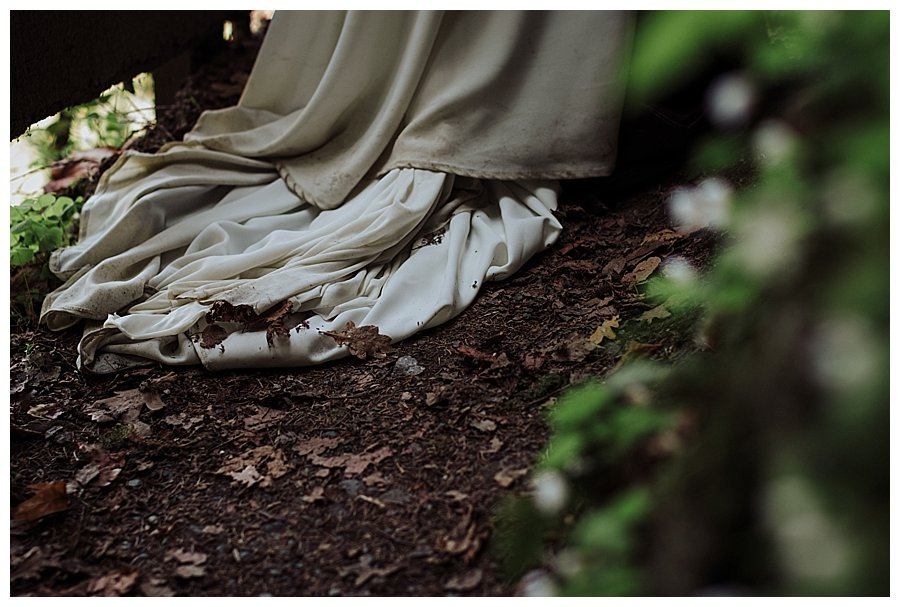 The bottom of a dirty wedding dress covered in dirt and leaves during a honeymoon trash the dress shoot in Austria by Wild Connections Photography