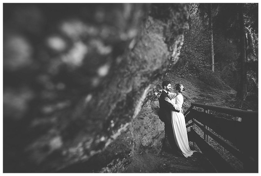 Bride leans on the groom who is leaning up against a rock