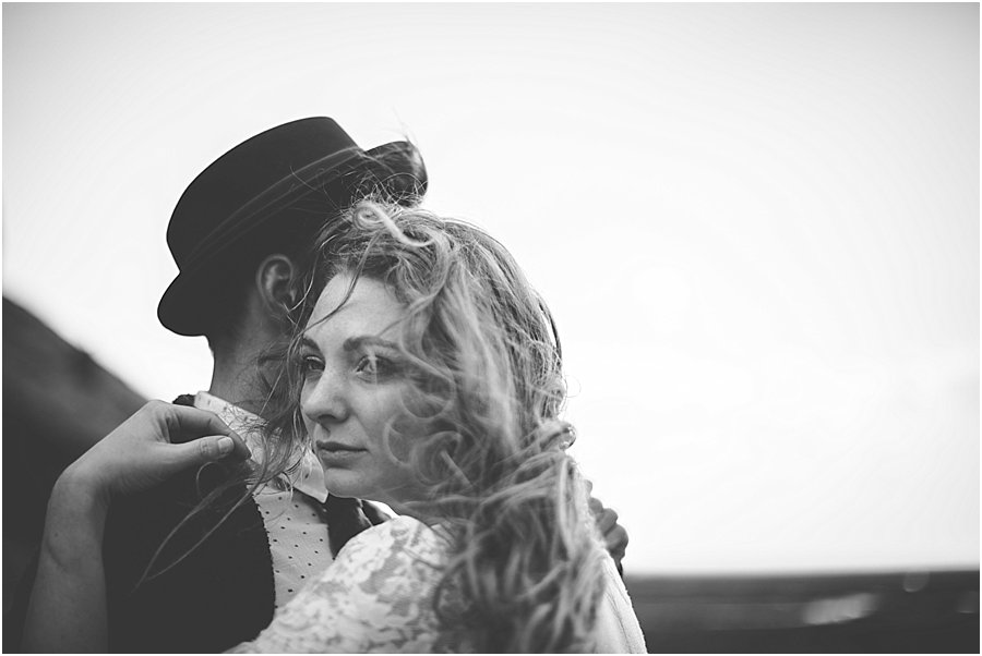 Bride and groom embracing as her hair blows in the wind