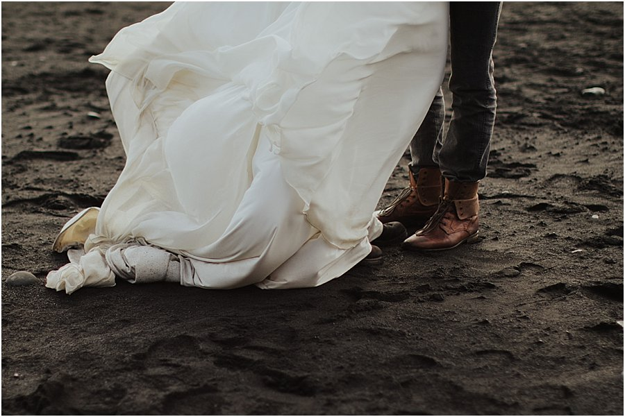 Black beach wedding picture of the shoes of the groom and the bottom of the bride's dress on the black beach at Vik by Wild Connections Photography