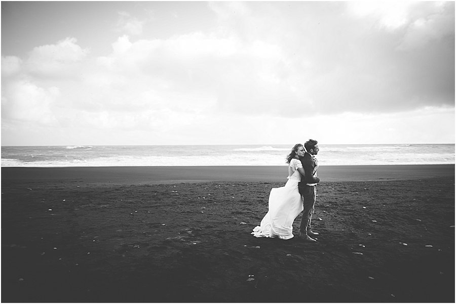 Iceland Black Beach Wedding photo with bride and groom embracing on the black beach by Wild Connections Photography