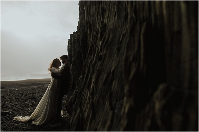 Bride and groom leaning against the rock wall