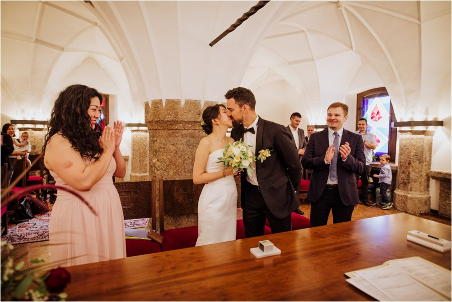 Kelly and Arik share a first kiss in the Innsbruck Standesamt under the golden roof by Wild Connections Photography