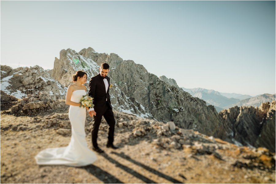 Kelly & Arik walk along the mountain path on their wedding day in Innsbruck by Wild Connections Photography