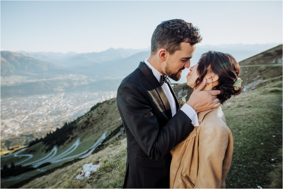 Sun sets over Innsbruck as Kelly and Arik share a kiss with the Inn valley in the background by Wild Connections Photography