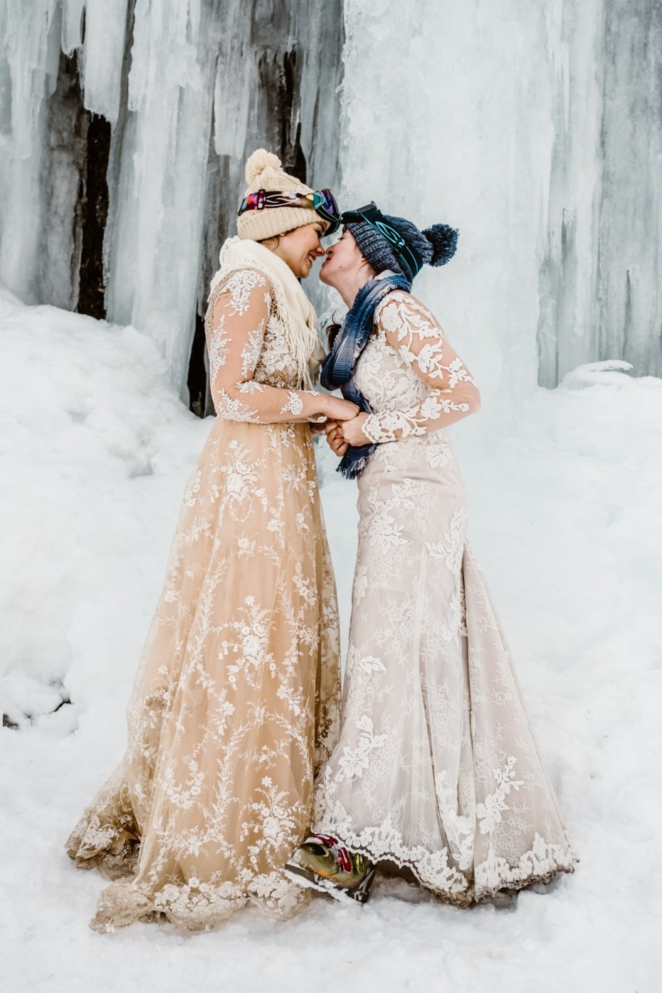 Two brides kiss under a frozen waterfall in Tirol in the Austrian Alps by Wild Connections Photography