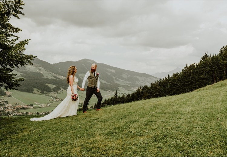 Kandler Alm mountain wedding in Austria couple walk up the hillside by Wild Connections Photography