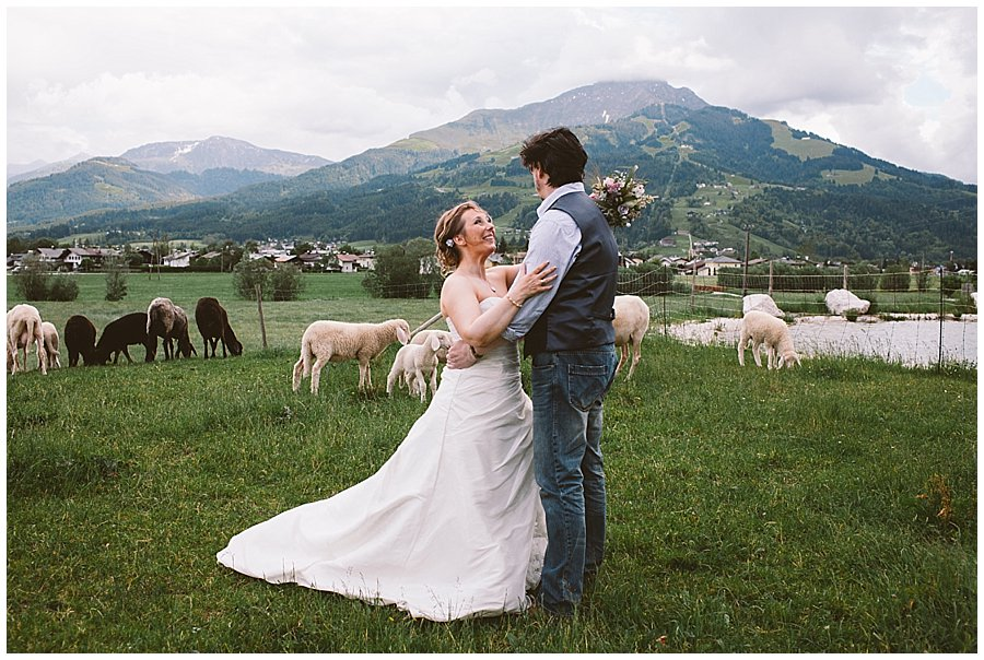 St Johann in Tirol Elopement Nikki and Chris stand in a field of sheep with mountains behind them by Wild Connections Photography