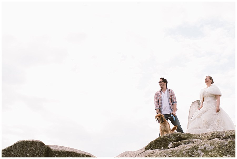 Wedding with Rescue Dogs - Husband and wife with one of their rescue dogs standing on the rocky mountain top by Wild Connections Photography