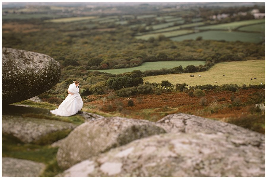 Wedding with Rescue Dogs - Distance shot of the bride standing on rocky mountain top over looking fields below by Wild Connections Photography