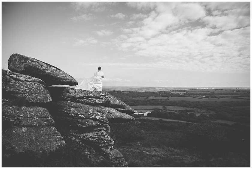Wedding with Rescue Dogs - Black and white photo of the bride standing on rocky mountain top over looking fields below by Wild Connections Photography