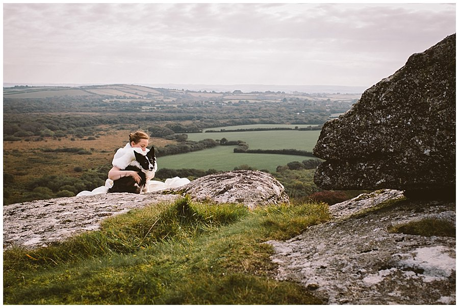 Wedding with Rescue Dogs - Bride sitting on rocky mountain top with one of her rescue dogs by Wild Connections Photography